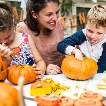 Mother and kids creating pumpkin art