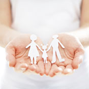 Woman holding paper cutout of family